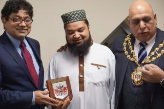 Helal receiving commemorative award from Oldham Council