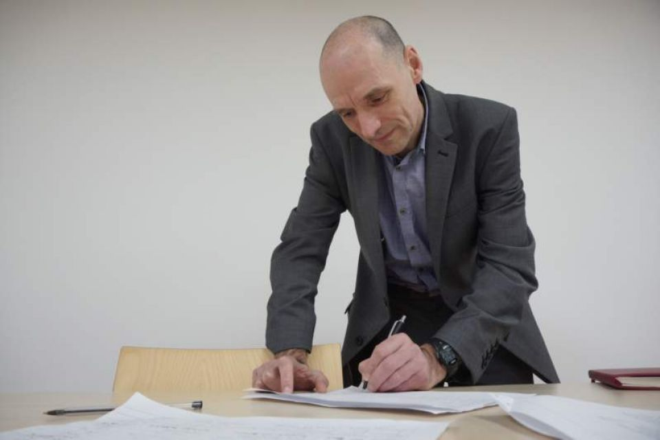 Bruce Penhale of Oldham Council signs